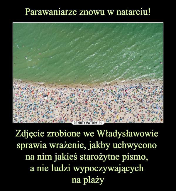 Zdjęcie zrobione we Władysławowie sprawia wrażenie, jakby uchwycono na nim jakieś starożytne pismo, a nie ludzi wypoczywających na plaży –